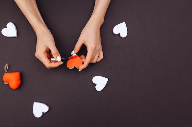 Руки девушки украшают красное сердечко в подарок любимой на день всех влюбленных. день святого валентина. в круге много белых сердечек. серый фон, вид сверху