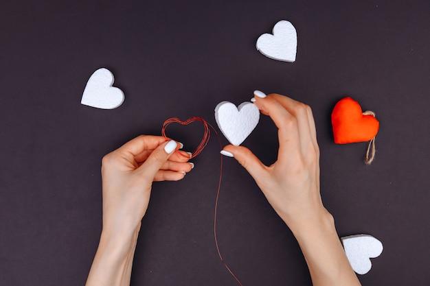 Руки девушки украшают белое сердечко в подарок любимой на день влюбленных. день святого валентина. в круге много белых сердечек.