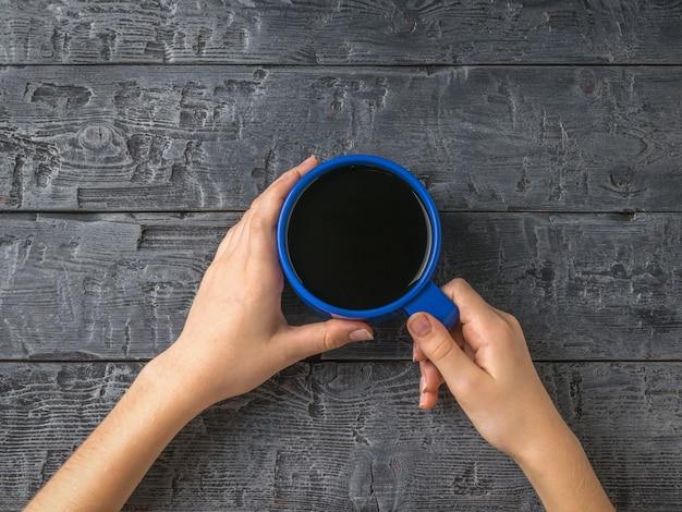 소녀의 손은 나무 테이블에 파란색 블랙 커피 한잔을 들고 있습니다. 인기있는 상쾌한 음료를 들고있는 여성의 손.