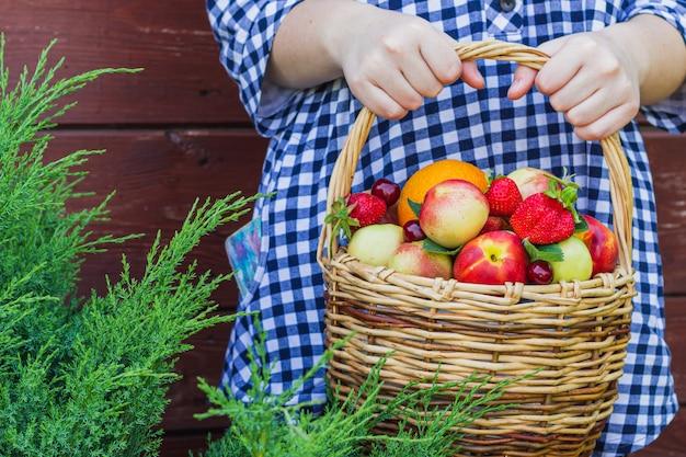В руках девушки нектарины, апельсины, клубника, вишня и листья мяты, которые лежат в плетеной корзине.