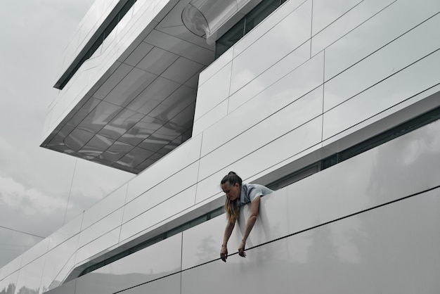 Голова и плечи девушки на фоне здания, руки свешиваются через забор. геометрия в строительстве.