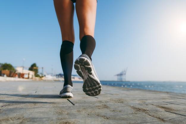 海の近くの夜明けに朝走る黒いゲートルと灰色のスニーカーの女の子の足