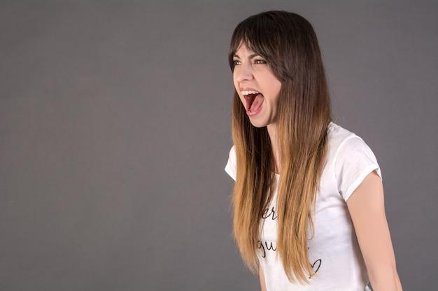 Девушка кричит с диким открытым ртом. понятие о гневе
