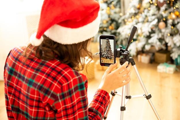 女の子は新年のブログを撮影するために電話を設定します。彼女はクリスマスの服を着ています
