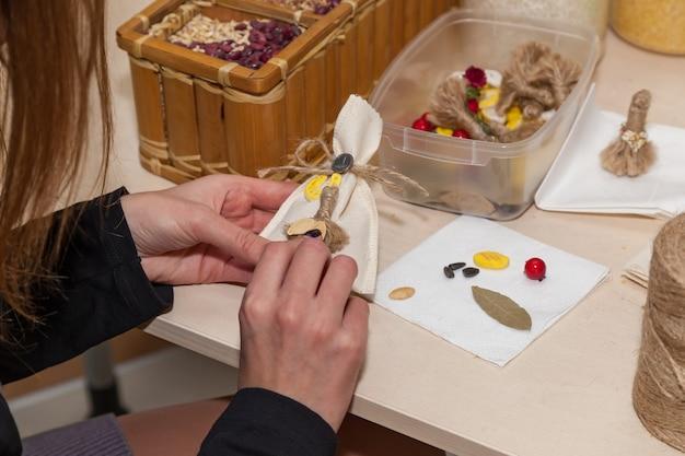 女の子は、さまざまな素材から人形やお守りを作成するマスタークラスを示しています人形m