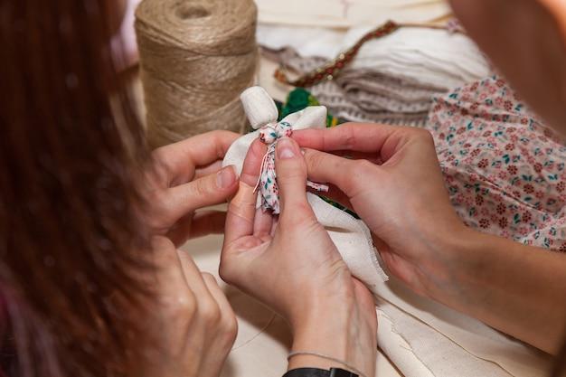 女の子は、さまざまな素材から人形やお守りを作成するマスタークラスを示しています