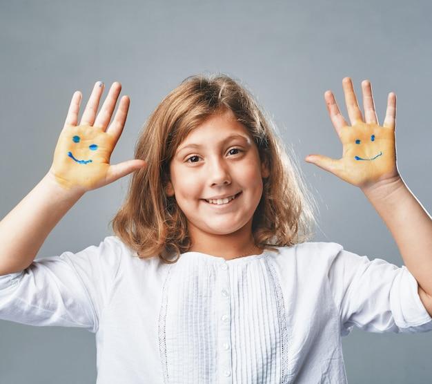 소녀는 그려진 이모티콘으로 손을 보여줍니다.