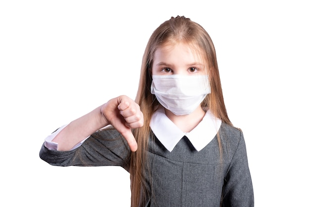 女の子は、医療用マスクが悪いことを示しています。白い背景で隔離。高品質の写真