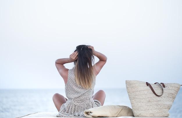 女の子は海のそばに座ってリラックスします