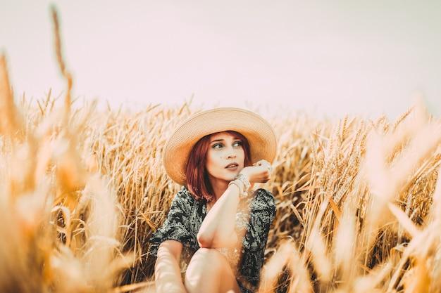 그 소녀는 황금빛 밀밭에 앉아 있다. 해질녘 밀 귀 사이에 낭만적인 모자를 쓴 어린 소녀.