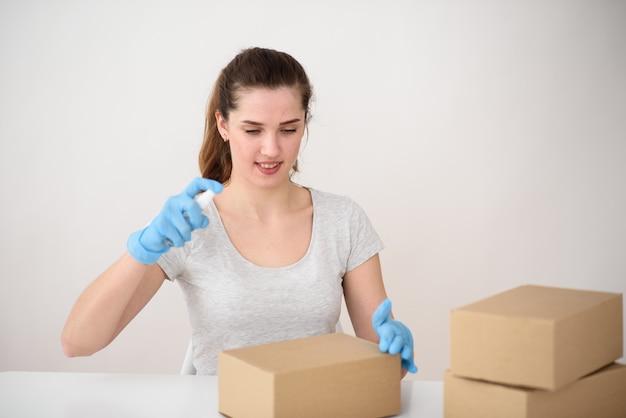 女の子はテーブルのゴム手袋に座って、段ボール箱に消毒剤を吐きます。安全な配達のコンセプト。ウイルスとの戦い