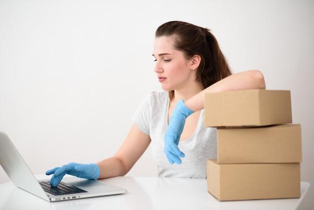 女の子はラップトップでタイプしているテーブルでゴム手袋に座っています。秒針は箱の上にあります。全世界での安全な配送のコンセプト。