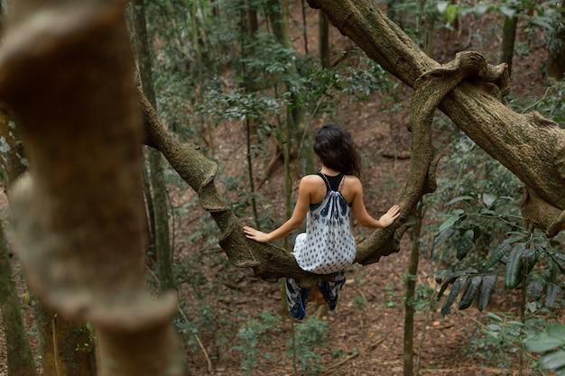 Девушка сидит на ветке огромной лианы в джунглях.