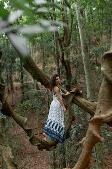 女の子はジャングルの巨大なつる植物の枝に座っています。