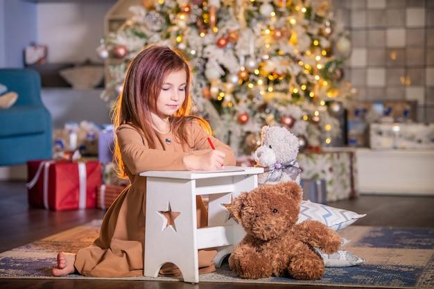 女の子はクリスマスツリーの前でひざまずいてサンタクロースに手紙を書きます。