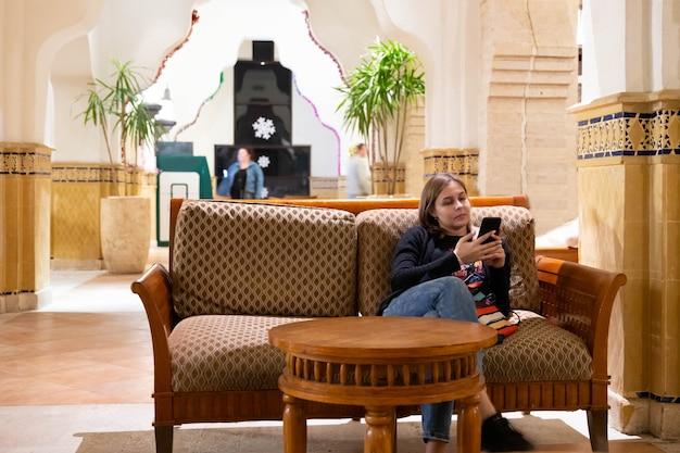 少女はホテルの受付のソファに座り、ホテルの部屋でチェックインを待っている間、電話を見ます。