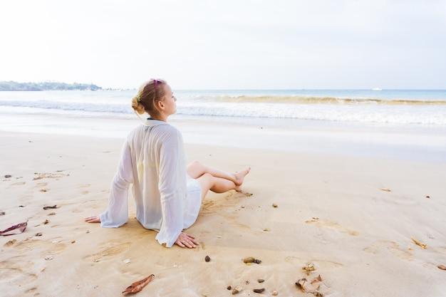 女の子は岸に座って海を見ます