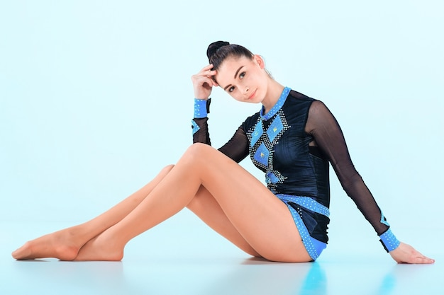 青い壁に体操ダンスの後に座っている女の子