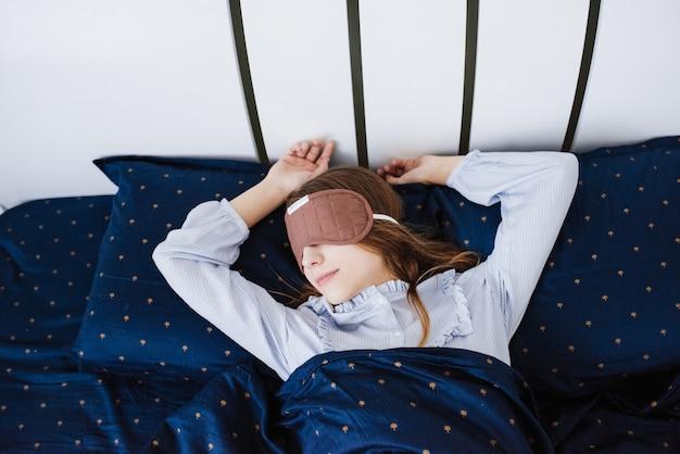 Девушка спит и лежит в пижаме в белом постельном белье. синяя кровать. с завязанными глазами на голове. маска для сна.