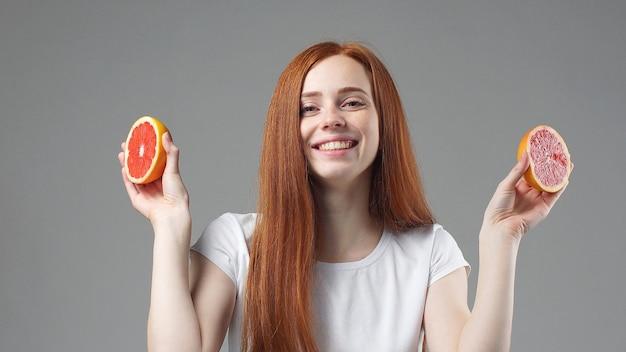 Девушка улыбается и держит половинки грейпфрута на сером фоне