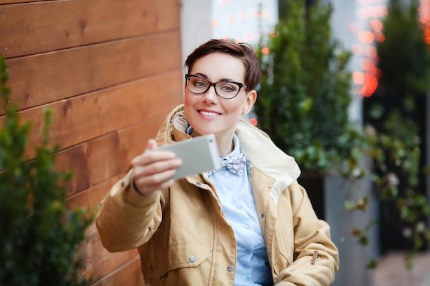 소녀는 미소 짓고 휴대 전화로 사진을 찍거나 현대 기술을 사용하여 회의를 이끌고 있습니다.