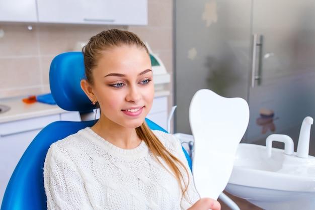 Девушка улыбается и смотрится в зеркало в стоматологии.