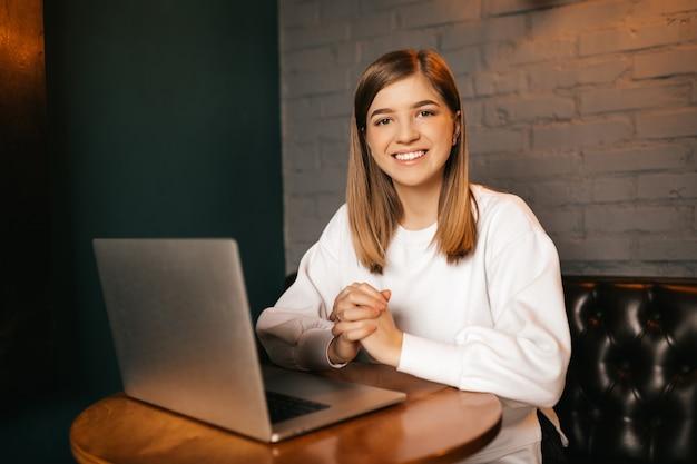 소녀는 컴퓨터에서 카메라에 미소 짓는다. 배경을 흐리게. 격리 된 배경.