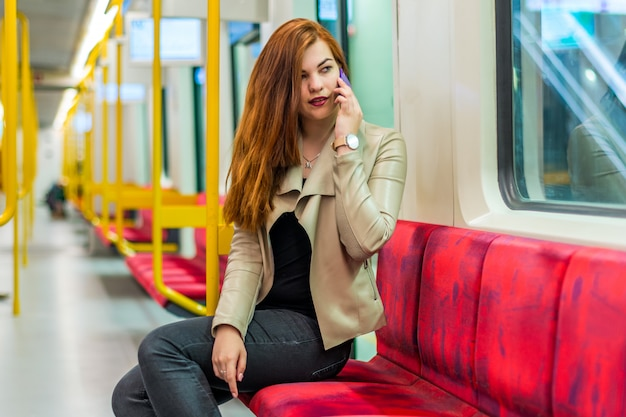 Девушка разговаривает по мобильному телефону в пустом поезде