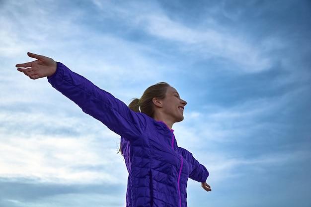 空に対して腕を広げている少女。