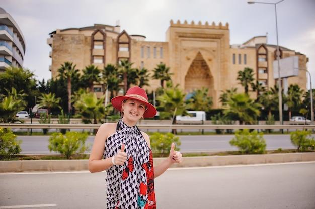 Девушка стоит возле гостиницы и показывает класс на пальцах. счастливая и улыбающаяся женщина. на фоне гостиницы. довольно стройная молодая девушка в красной шляпе и платье. турция.