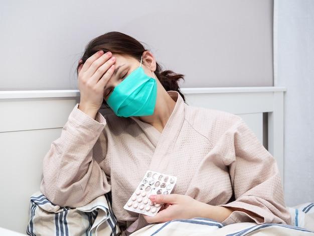 少女は頭痛に苦しみ、薬を飲み、自宅で検疫に横たわっています。
