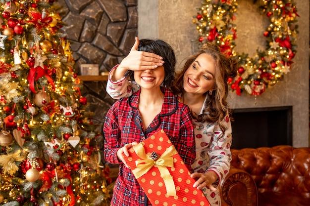 크리스마스 선물로 친구를 놀라게하는 소녀. 황금 리본으로 그녀의 손에 큰 빨간 상자를 들고 여자 친구.