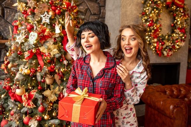 소녀는 선물로 친구를 놀라게했다. 그녀의 손에 들고 여자 친구 레드 골든 리본으로 존재. 그들은 매우 행복해 보입니다. 그들은 크리스마스 파자마를 입고 있습니다.