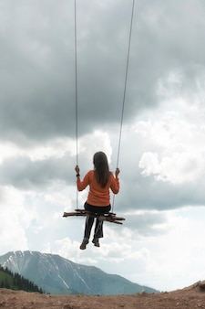 Девушка качается на качелях над горами, ощущение полета и свободы.