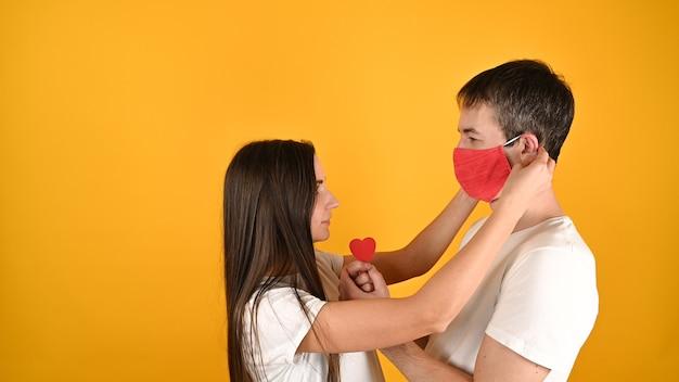 Девушка снимает с парня маску на желтом