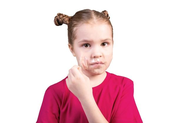 女の子は白い背景で隔離の彼女の口に貼り付けられた粘着テープをはがします