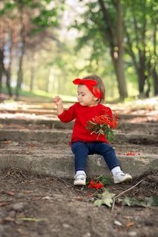 女の子は花束から赤いナナカマドの果実を引き裂き、地面に投げます