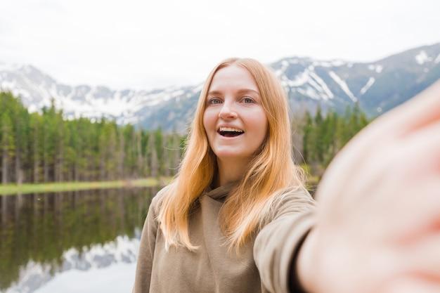 Девушка-турист, делающая селфи в горном озере. смотрю в камеру и улыбаюсь. концепция путешествий и активной жизни. на открытом воздухе