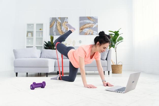 소녀는 피트니스를 위해 탄성 밴드로 집에서 온라인으로 훈련합니다. 노트북을 가진 여성을위한 온라인 가정 교육. 격리 된 집에서 스포츠.
