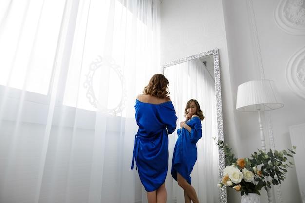 소녀는 거울 맞은 편에있는 탈의실에서 옷을 입는다