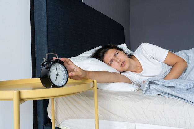 Девушка выключает надоедливый будильник, чтобы продолжить спать. высыпай еще немного. утро тяжелое. время просыпаться.