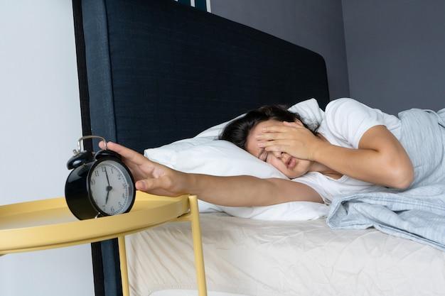 女の子は迷惑な目覚まし時計をオフにして眠り続けます。もう少し寝ます。これはハードな朝です。起きる時間。