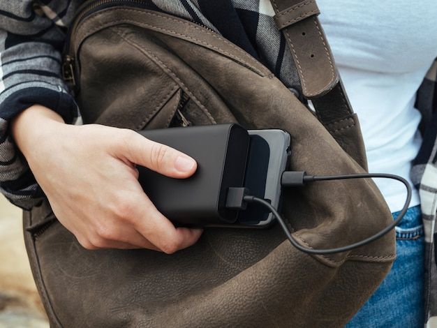소녀는 파워 뱅크에 연결된 스마트 폰을 사용합니다.