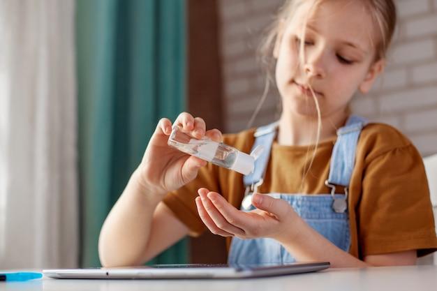 Девочка использует антисептический гель для рук на спиртовой основе, выполняя домашнее задание с помощью планшета. профилактика, дезинфекция рук, профилактика инфекций, вспышка covid-19