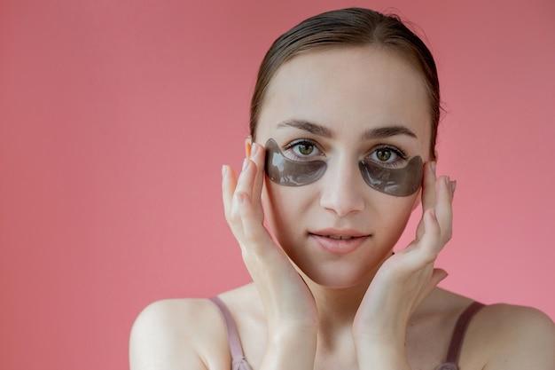 Девушка использует черные пятна под глазами, улыбаясь, сидя напротив зеркала. здоровый образ жизни, молодость, уход за лицом.