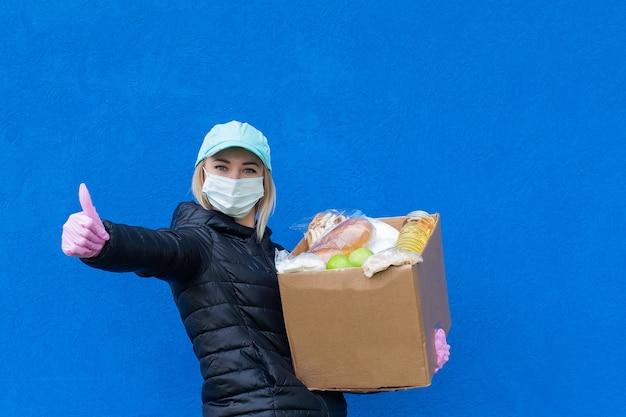 Девушка-волонтер с благотворительной коробкой на синем фоне
