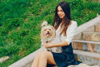 The girl walks in the park with her dog