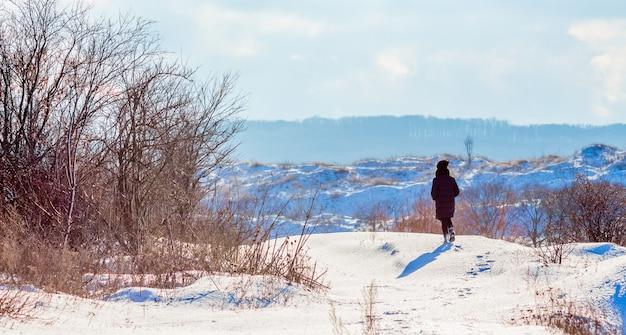 女の子は自然の中で冬を歩きます。冬の晴れた日。自然の中で孤独な女性