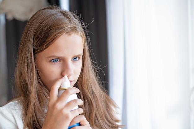소녀는 바닷물 스프레이로 코를 씻습니다.