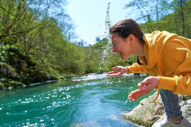 소녀는 산 강에서 맑은 물로 몸을 씻습니다. 산에서 하이킹